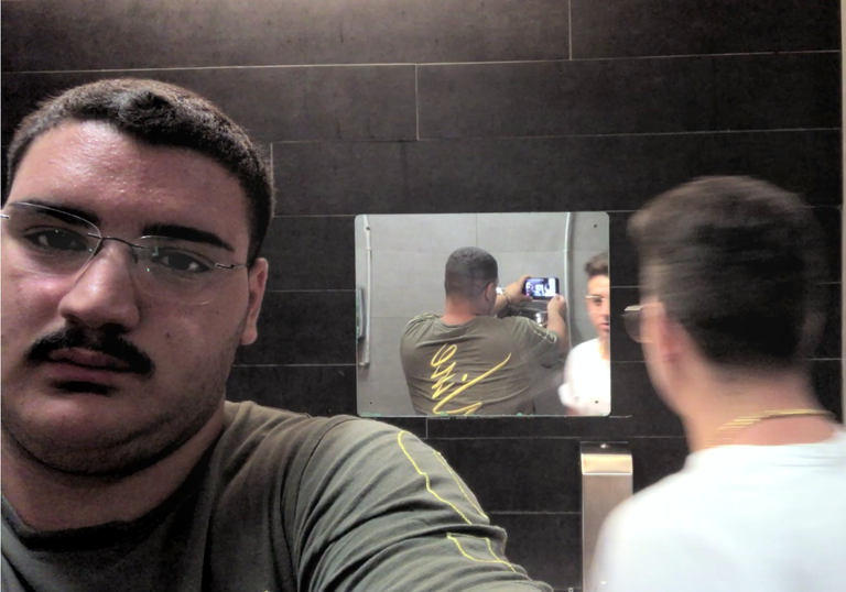 A man takes a selfie in a bathroom and we see this reflected in a mirror opposite, while a friend looks directly into the mirror