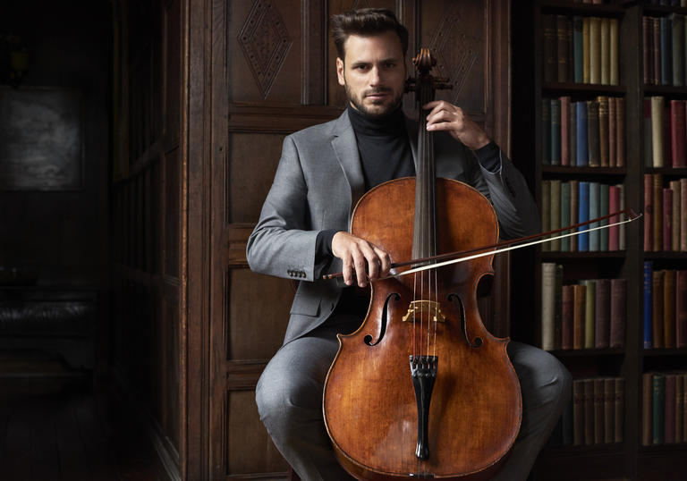 Stjepan Hauser playing cello in front of bookcase