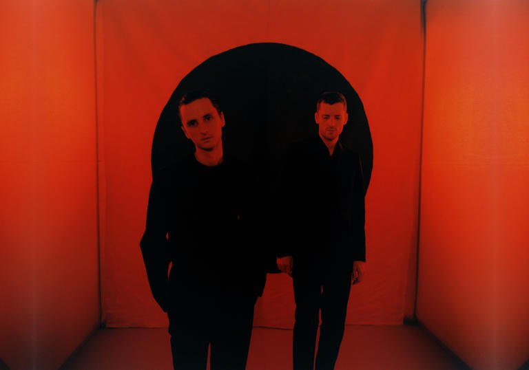 These New Puritans standing in a red room