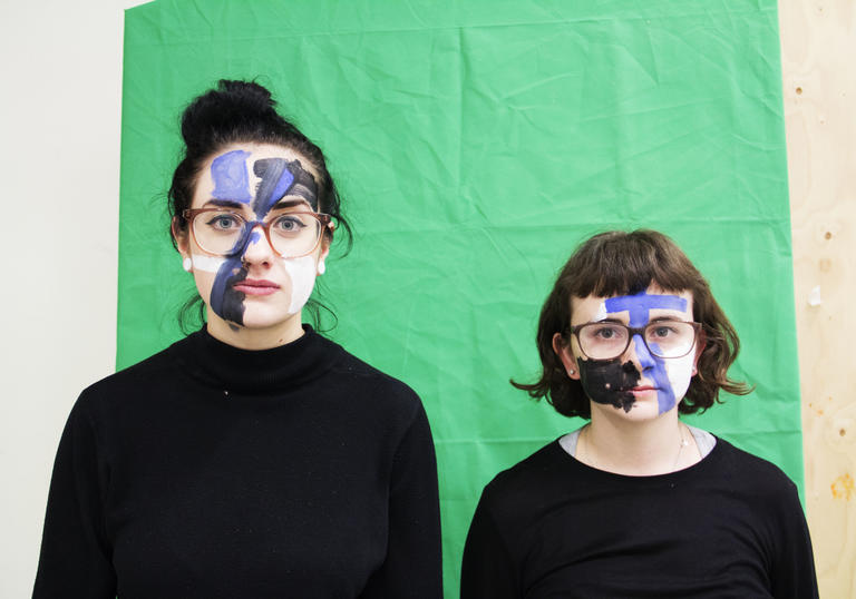 Two women, standing in front of a green screen with paint on their face