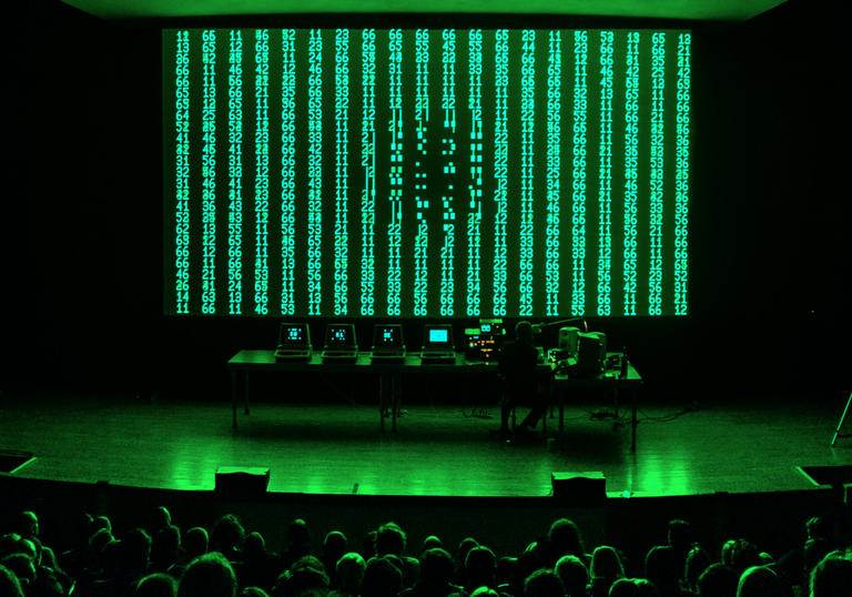 image of live performance shows robert henke standing in front of green and back digital screen with a bank of computers and electronics set up