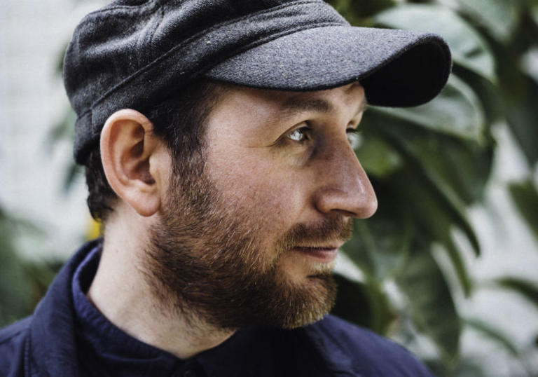 photo of Matthew Halsall's face. He has a beard and is wearing a cloth hat. In the background is an out of focus green plant