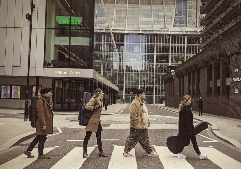 Four Guildhall students on zebra crossing in style of The Beatles' Abbey Road album