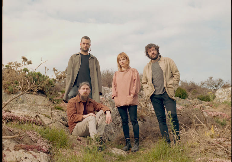 photo of the 4 band members in the countryside. They are surrounded by grass and rocks. 3 are standing, one is sitting and they face the camera