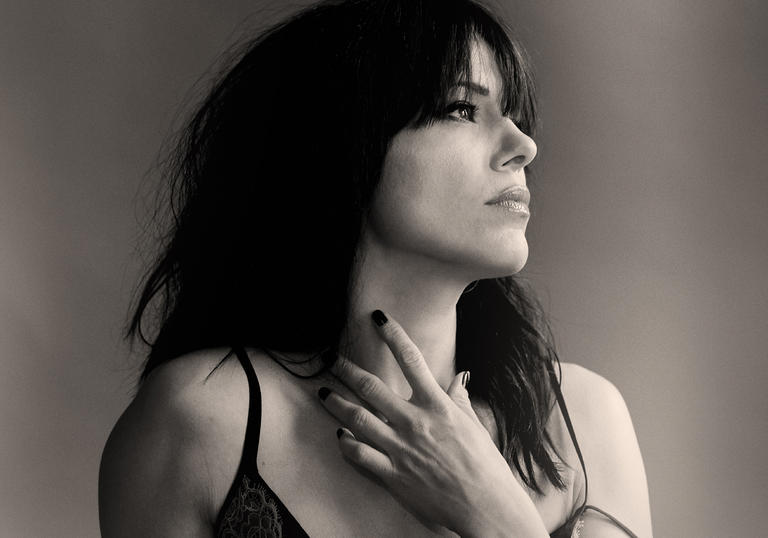Imelda May looking to the left and holding her hand up to her neck