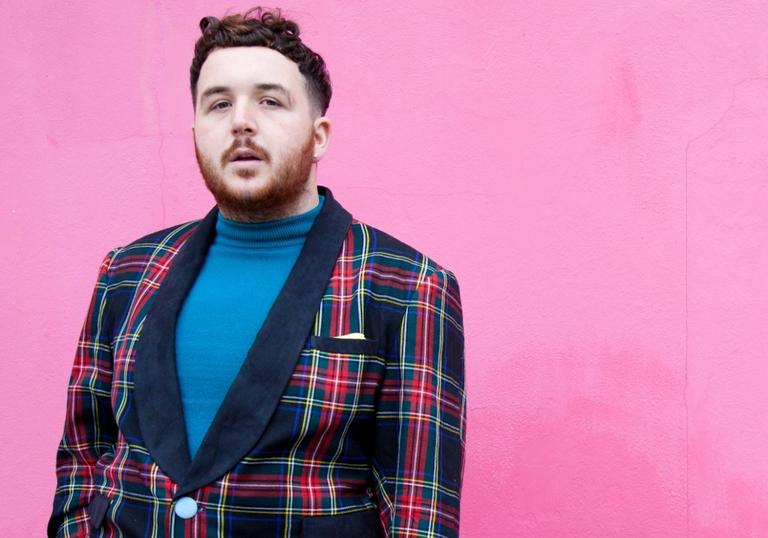 An image of Scotte standing against a vivid pink wall wearing a suave tartan two-piece suit