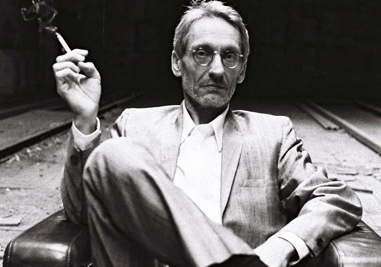 black and white photo of Manuel Göttsching sitting in a chair smoking a cigarette with his legs crossed