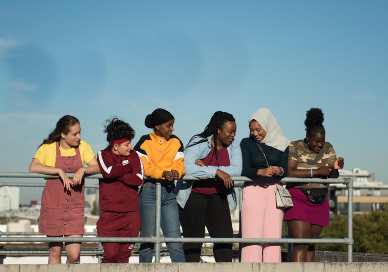 A group of girls stand in a line talking and laughing