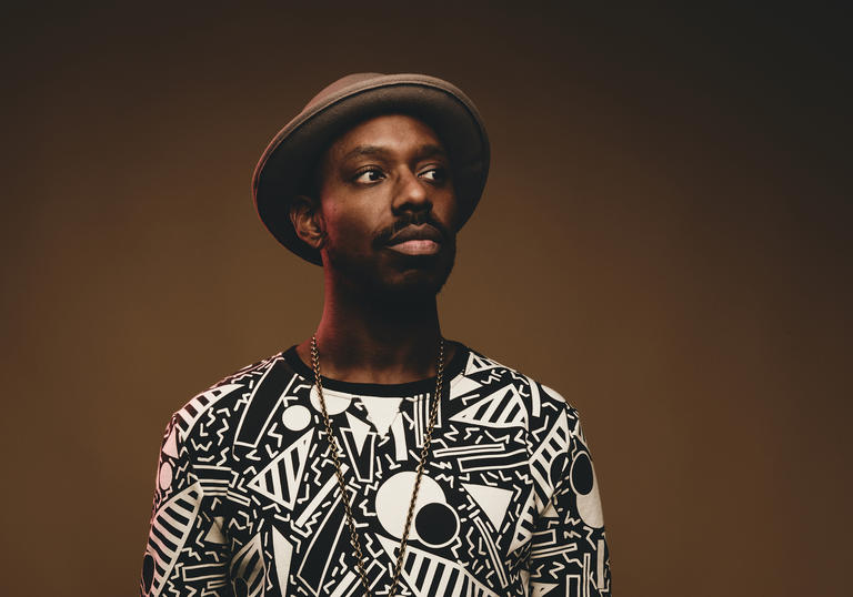 Shabaka Hutchings wearing a patterned top and hat, looking to his left.