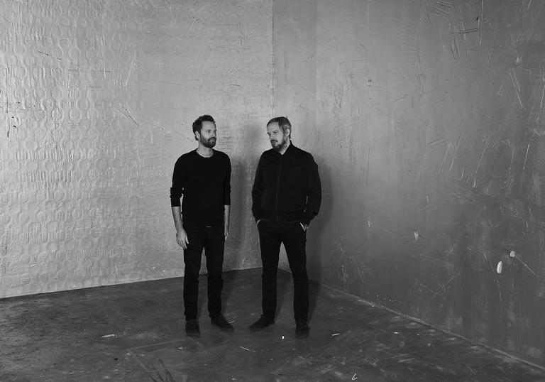 Dustin O'Halloran and Adam Wiltzie standing in a bare room, wearing all black.