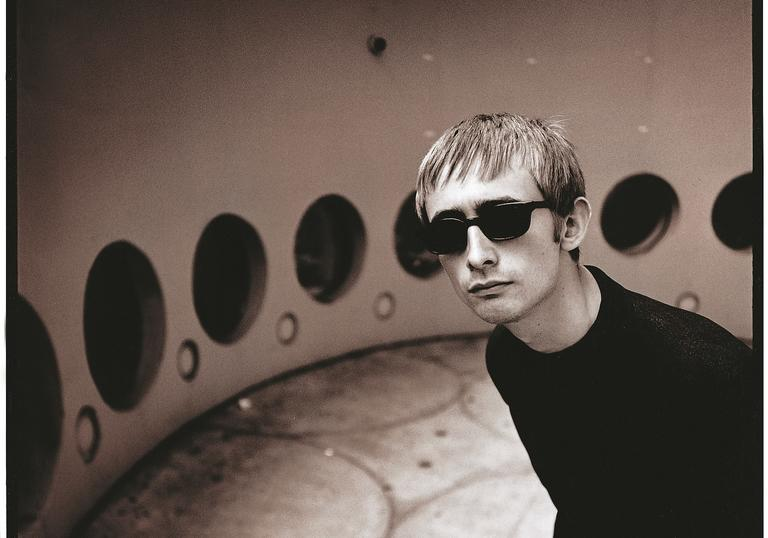 Black and white photo of Neil Hannon in a retrofuturistic room with black circular windows