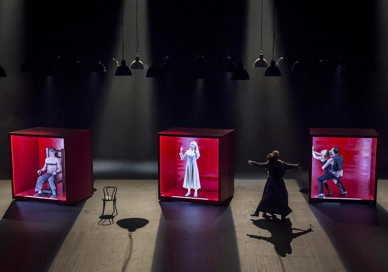 three people in red cubes on a stage