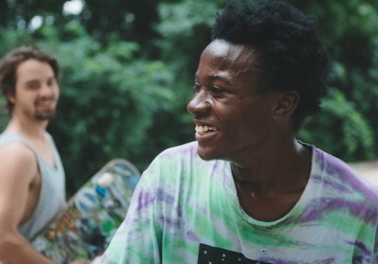 Two men are laughing, one is in the background holding a skateboard