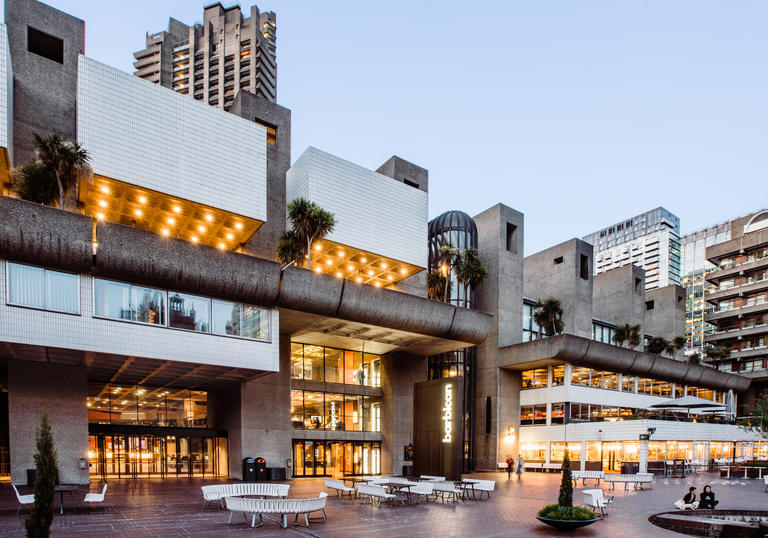 Image of the Barbican Lakeside terrace in early evening with lights glowing
