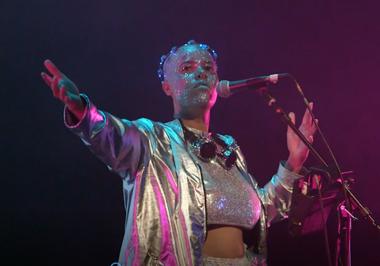 photo of a performer wearing glitter and holding a microphone