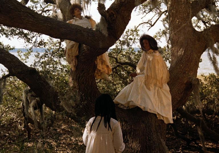 two women wearing white gowns next to big trees