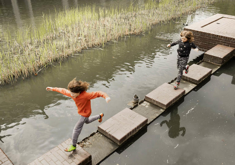 Child jumping on lakeside