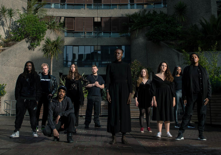 10 Guildhall PACE students dressed in black standing in sunshine on Barbican estate