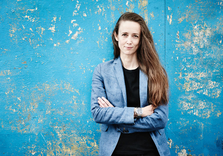 Conductor Jessica Cottis standing against a blue patterned wall with arms crossed