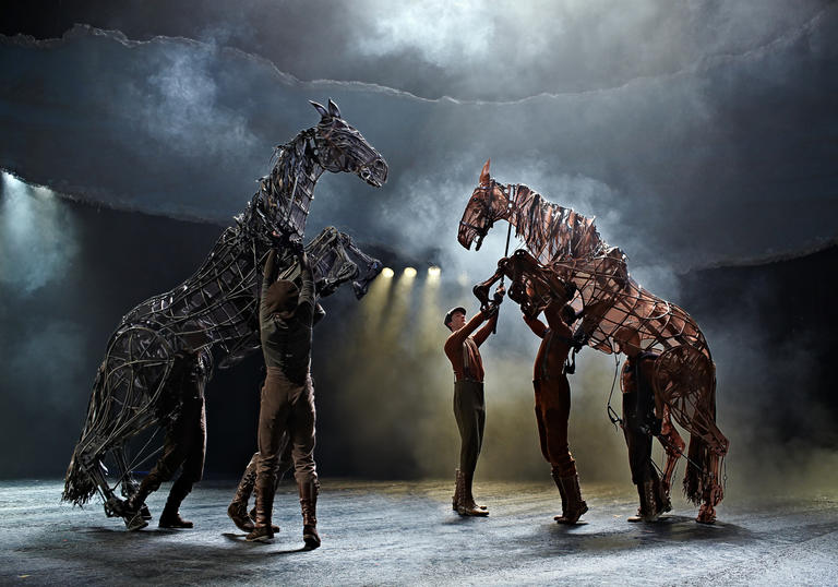 puppet horses rearing on their hind legs whilst men are trying to control them
