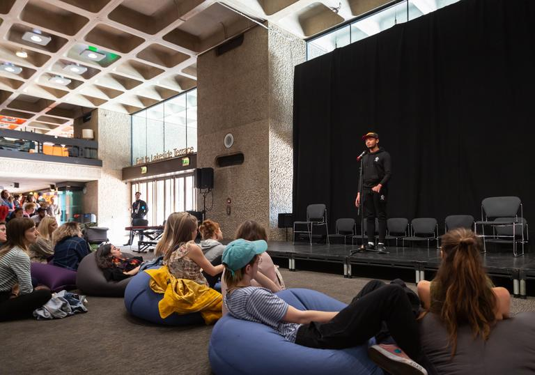 A group of people are sat on beanbags on the floor watching a person on stage