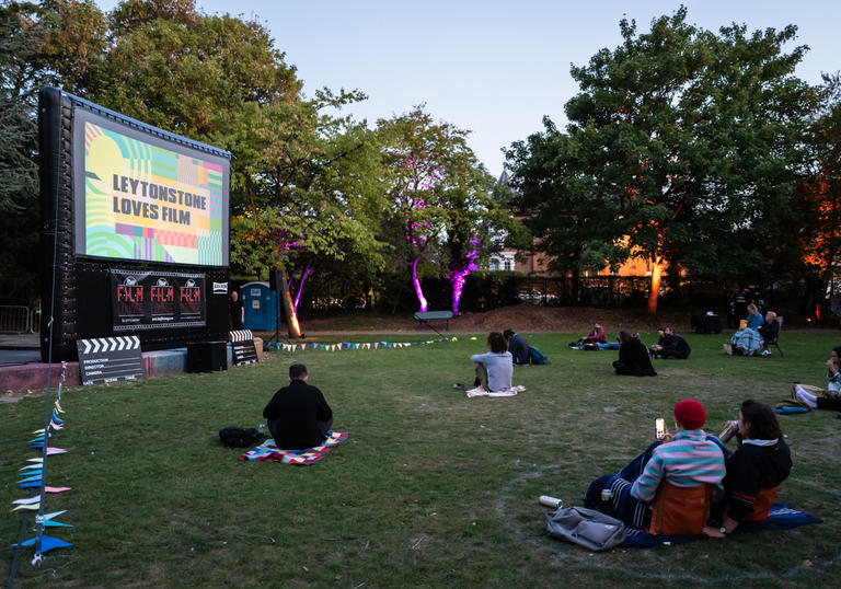 Groups of people are sat watching a screen with a movie showing in a park