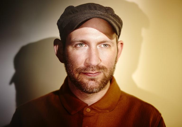 photo of Matthew Halsall wearing a cap and shirt against a plain backgound, being lit from multiple sources to create shadows