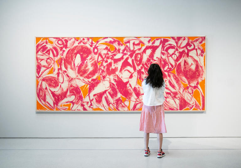 A woman standing in front of a Lee Krasner painting