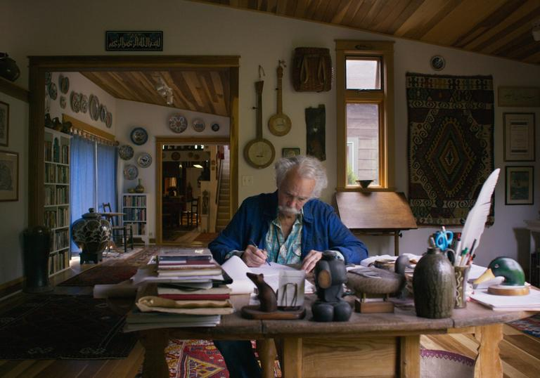 Henry Glassie sit in his office surrounded by artifacts