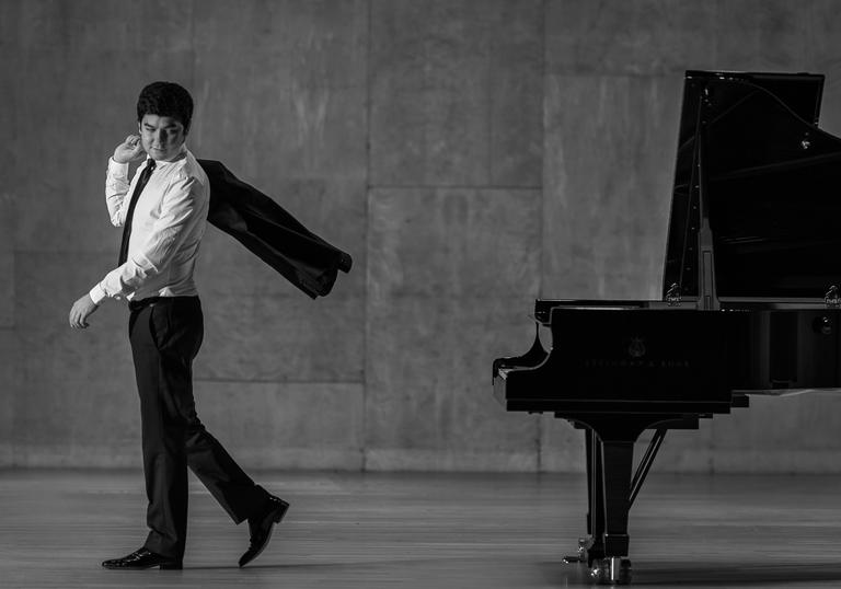 A black & white picture of Behzod Abduraimov walking away from a piano