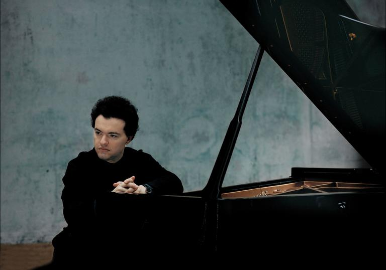 A colour photograph of Evgeny Kissin by a piano