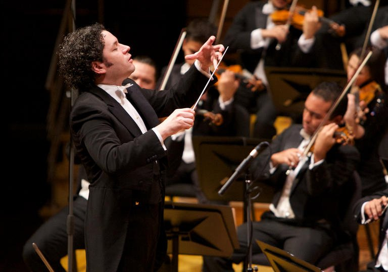 A full colour photograph of Gustavo Dudamel conducting