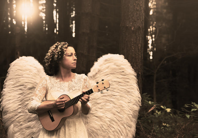Kate Rusby dressed as an angel holding a ukelele and staring into the distance