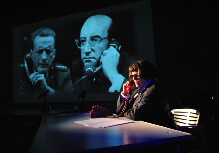 A photo showing a character called Lois Weaver in glasses, wearing a black jacket on the phone. It is a red coloured phone and is on a table with some paper. In the background there is a clip from Dr. Strangelove the film