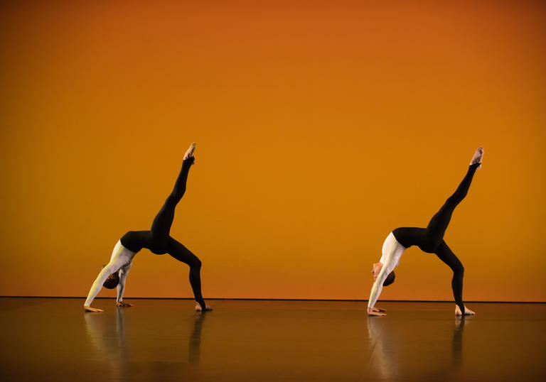 A photo of two dancers from the Michael Clark Company against an orange background.