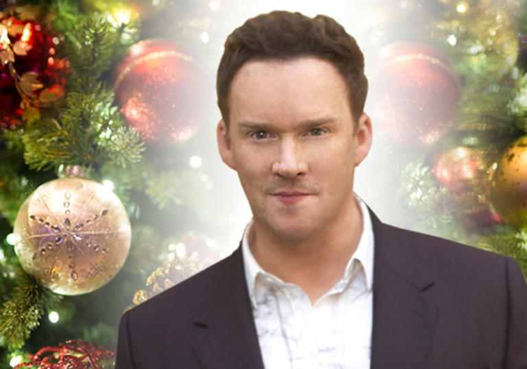 Image of Russell Watson against a backdrop of Christmas decorations