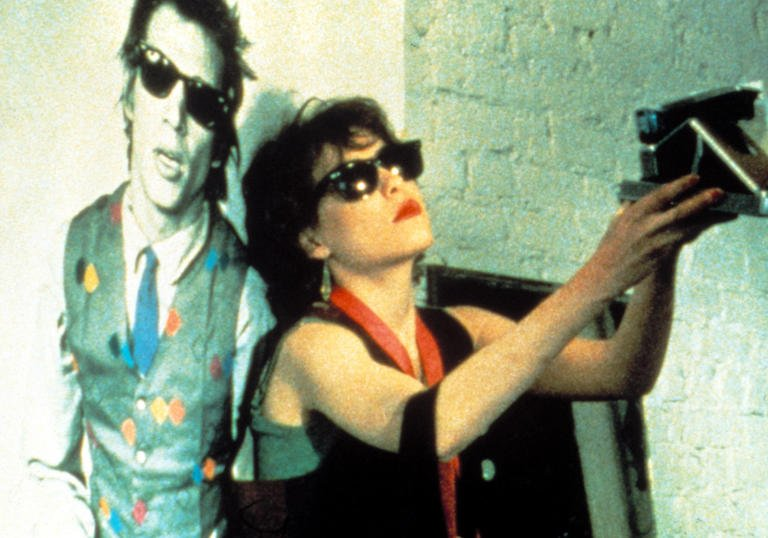 Photo still from Smithereens film of woman in sunglasses taking a Polaroid photo