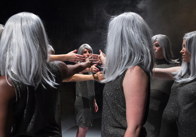 Photos which shows a group of women with identical silver wigs holding their hands out into a circle