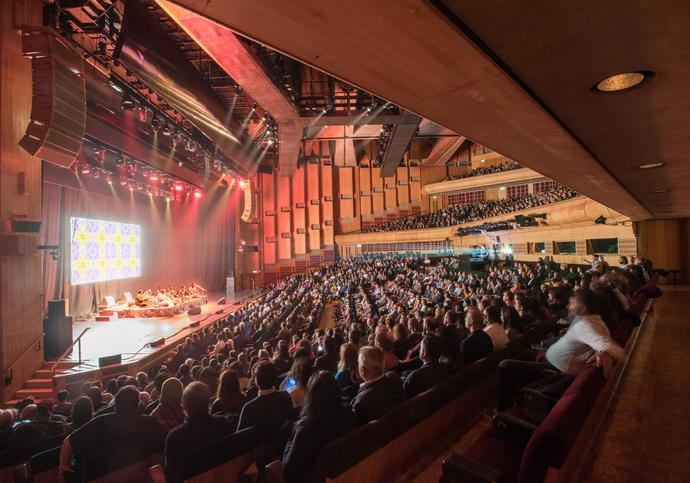 Photo of music performance and a full audience in the Barbican Hall