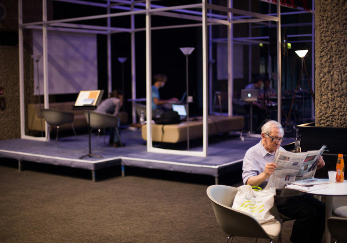 Photo of old man reading newspaper in the Barbican foyers during Hack the Barbican