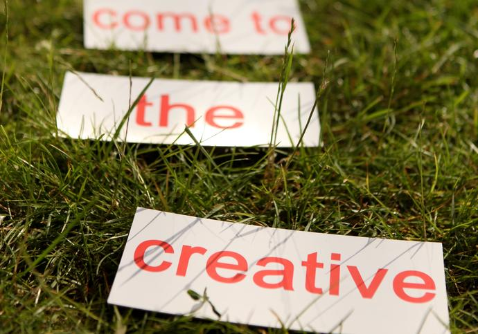 words lie on the grass inviting you to come to the creative. Come we shall