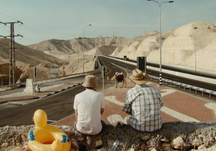 Two men sit on a wall looking out into the road into the distance, where a camel is standing