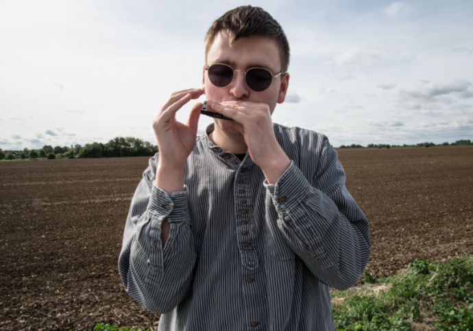 a young man with sunglasses and a harmonica