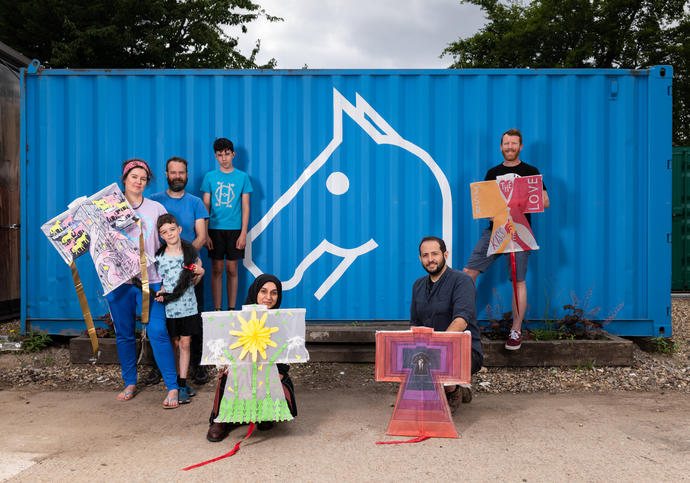 A group of people stand in front of a blue metal box with an image of a horse on it holding kites that they have made