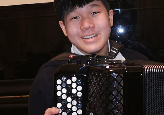 Smiling boy holding an accordion