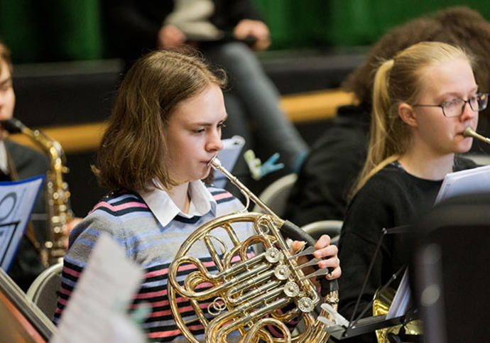 Girl playing french horn in orchestra