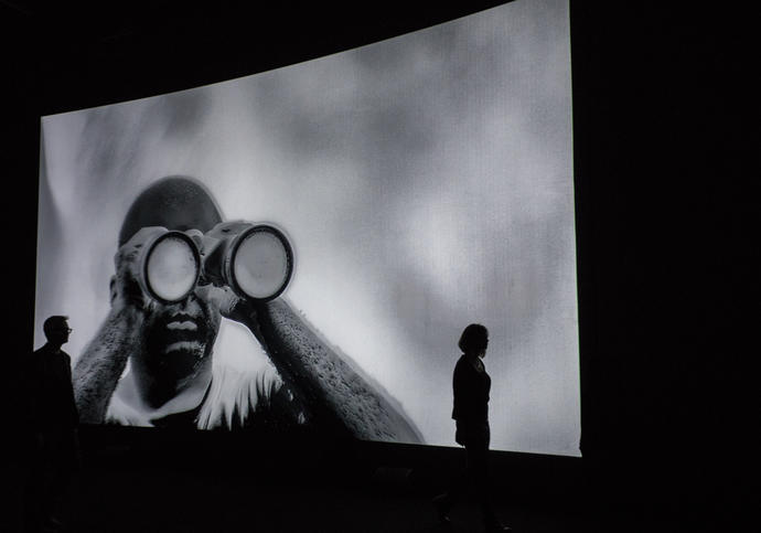 Photo of figure watching screen projections by Richard Mosse Incoming