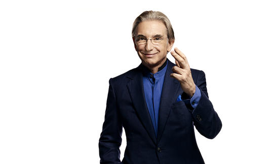 Photo of Michael Tilson Thomas wearing a black suit and blue shirt
