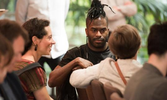 Photo of man with dreadlocks in the crowd at a symposium