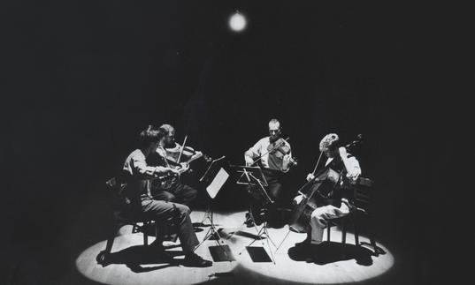 Kronos Quartet performing while bathed in a dreamy white light